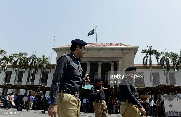 Pakistani police officers walk outside the Punjab province assembly during the oath taking ceremony of newly elected provincial lawmakers in Lahore...