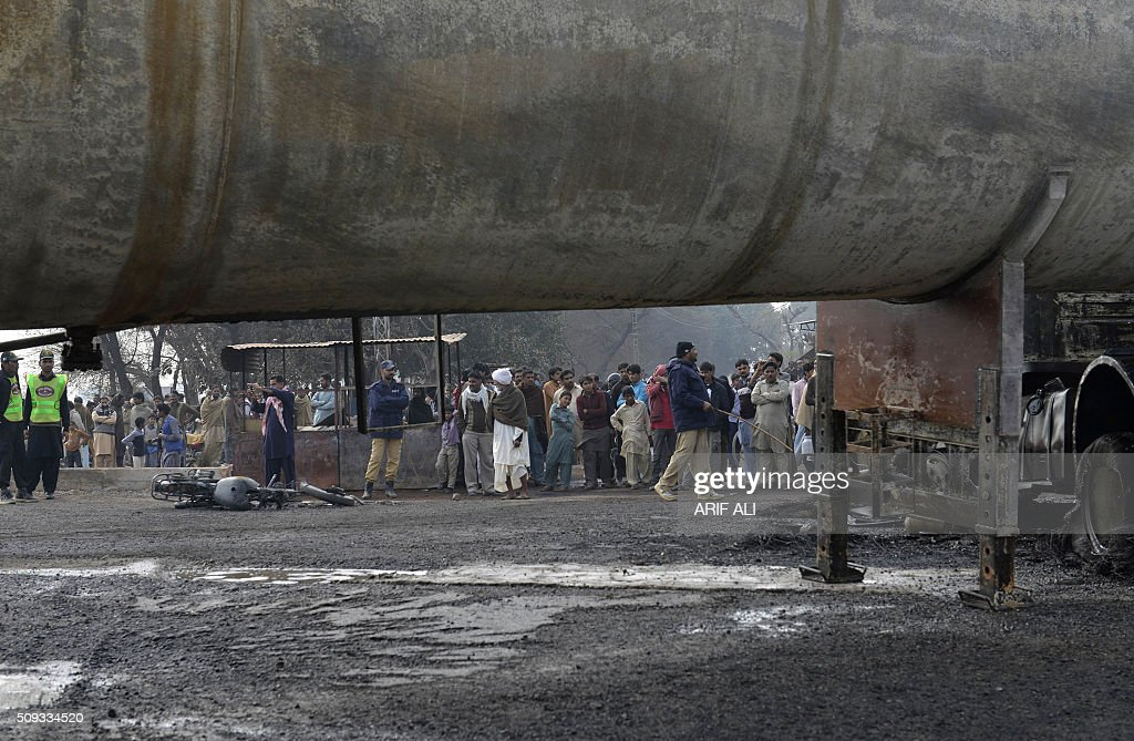 Pakistani police officials and residents stand near wreckage of a burnt out a tanker that collided with a car in the district of Sheikhupura in Pakistan's most populous Punjab province on February 10, 2016. Six schoolchildren were among at least 10 people killed when a fireball erupted as a tanker carrying liquefied petroleum gas (LPG) collided with a car in eastern Pakistan, engulfing surrounding vehicles, officials said. AFP PHOTO / ARIF ALI / AFP / Arif Ali