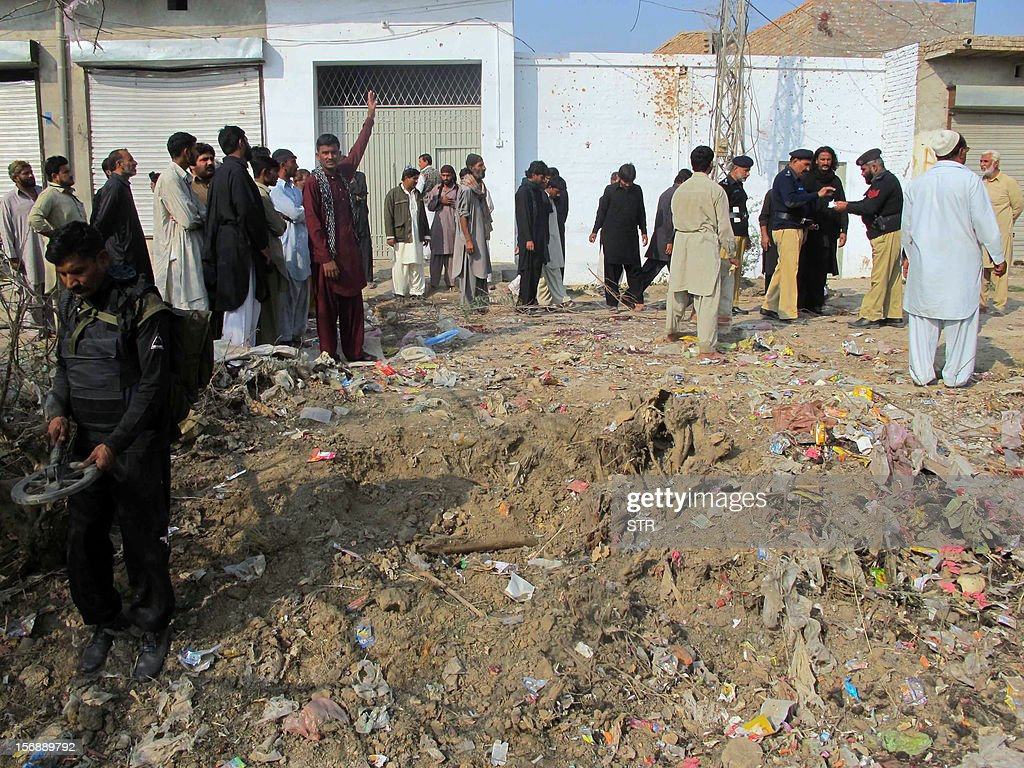 Pakistani police officials and Shiite Muslims inspect the site of a bomb explosion on the outskirts of Dera Ismail Khan in Khyber Pakhtunkhwa province on November 24, 2012. A bomb exploded near a Shiite religious procession in northwest Pakistan on November 24 killing seven people including four children, hospital officials said. The blast went off as people from the minority Shiite Muslim community were gathering to mark the anniversary of the death of the Prophet Mohammed's grandson Imam Hussain in 680.