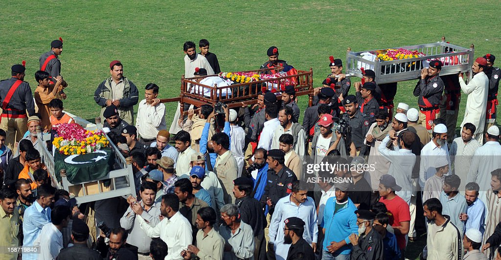 Pakistani police officials carry coffins of their colleagues during a funeral in Karachi on December 26, 2012, after they were killed during an attack by gunmen on a vehicle. Gunmen opened fire on a car carrying a senior figure from an extremist Muslim Sunni group in the Pakistani city of Karachi on December 25, killing four policemen and two other people, police said. AFP PHOTO/ASIF HASSAN
