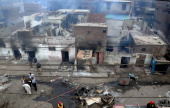 Pakistani police officials examine the burnt out houses of members of the Christian community attacked by Muslim demonstrators during a protest over...