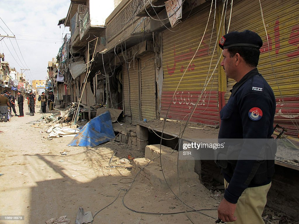 Pakistani police officials inspect the site of a bomb explosion in the city of Dera Ismail Khan in Khyber Pakhtunkhwa province on November 25, 2012. A bomb attack on a Shiite Muslim procession killed three people and wounded more than 50 in northwest Pakistan on November 25 as Shiites marked their holiest day Ashura, police said. AFP PHOTO / STR