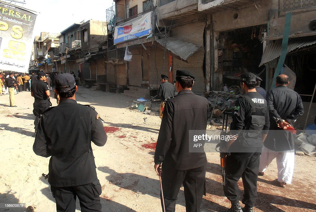 Pakistani police officials inspect the site of a bomb explosion in the city of Dera Ismail Khan in Khyber Pakhtunkhwa province on November 25, 2012. A bomb attack on a Shiite Muslim procession killed three people and wounded more than 50 in northwest Pakistan on November 25 as Shiites marked their holiest day Ashura, police said. AFP PHOTO/NASEER AZAM