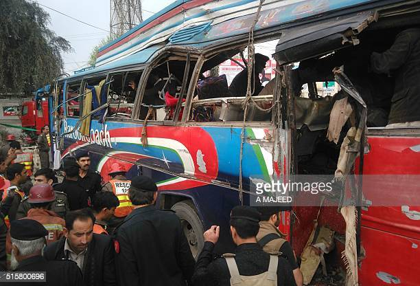 Pakistani police officials search a damaged bus after a bomb blast in Peshawar on March 16 2016 A blast ripped through a bus carrying government...
