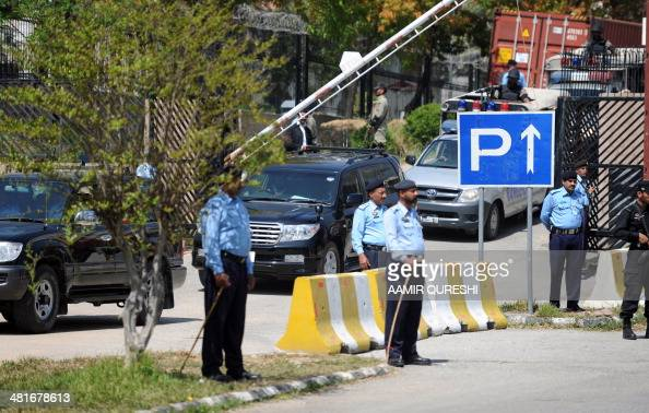 Pakistani police stand guard as the vehicle carrying former military ruler Pervez Musharraf leaves a special court after a hearing in Islamabad on...