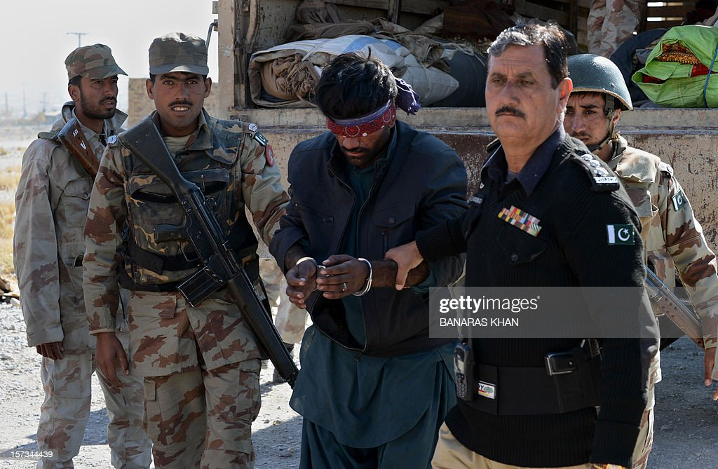 A Pakistani policeman (R) and paramilitary soldiers escort an arrested suspect into a police station in Quetta on December 2, 2012, after police recovered tonnes of potassium chlorate from a bus. Pakistani authorities seized nearly 14 tonnes of potassium chlorate, a key ingredient in bomb-making, from a bus in the country's violent and unstable southwest on Sunday, officials said. AFP PHOTO/Banaras KHAN