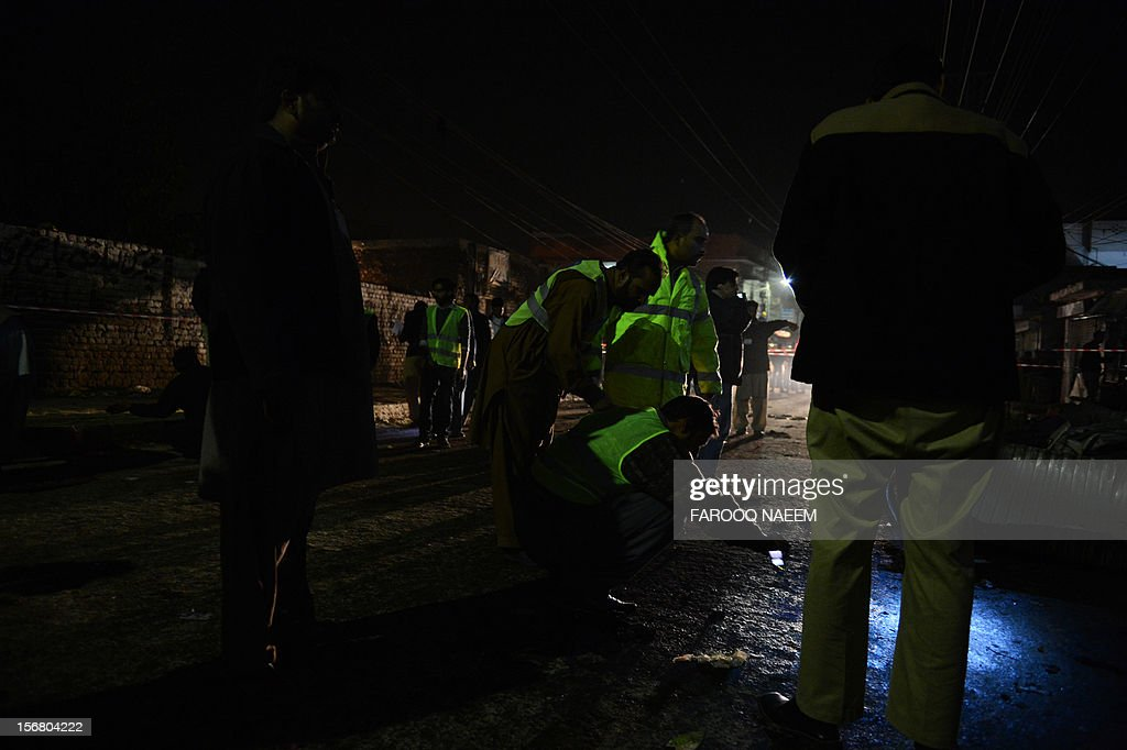 A Pakistani policeman collects evidence at the bomb blast site in Rawalpindi on November 22, 2012. A blast during a religious procession on Wednesday left at least six people dead and several others injured in the city of Rawalpindi in an attack by a suicide bomber, police said. AFP PHOTO/Farooq NAEEM
