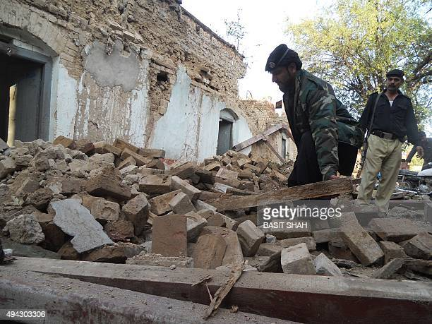 A Pakistani policeman digs through the debris of collapsed houses after an earthquake in Kohat on October 26 2015 A powerful 75 magnitude earthquake...