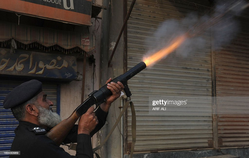 A Pakistani policeman fires tear gas towards Christian demonstrators during a protest against the attack on the homes of members of the Christian community by Muslim demonstrators in Lahore on March 10, 2013. Christians demonstrated around Pakistan on March 10 to protest after a Muslim mob torched more than 100 Christian homes following allegations of blasphemy. More than 3,000 Muslims rampaged through Joseph Colony, a Christian area of the eastern city of Lahore, on March 9 after allegations that a Christian had made derogatory remarks about the Prophet Mohammed three days earlier.