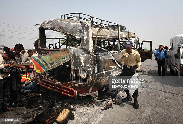 A Pakistani policeman inspects a burnt bus after the compressed natural gas cylinders powering it exploded while it was on a highway on the outskirts...