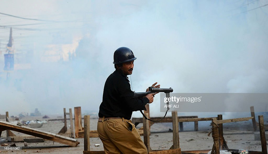 A Pakistani policeman looks on after firing tear gas towards Christian demonstrators during a protest against the attack on the homes of members of the Christian community by Muslim demonstrators in Lahore on March 10, 2013. Christians demonstrated around Pakistan on March 10 to protest after a Muslim mob torched more than 100 Christian homes following allegations of blasphemy. More than 3,000 Muslims rampaged through Joseph Colony, a Christian area of the eastern city of Lahore, on March 9 after allegations that a Christian had made derogatory remarks about the Prophet Mohammed three days earlier.