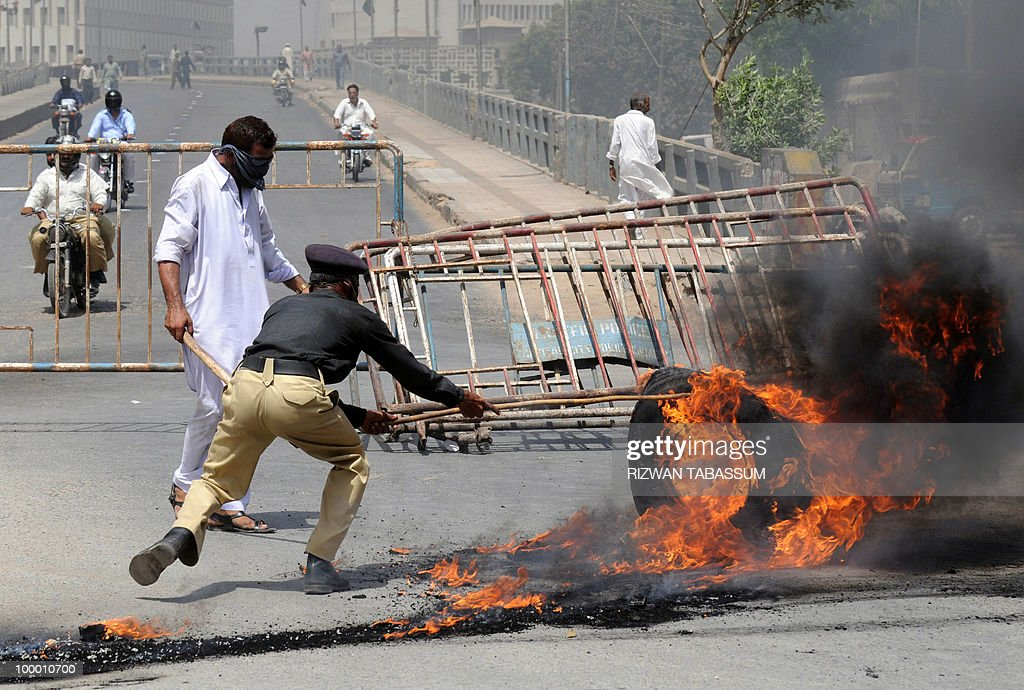 A Pakistani policeman removes burning tyres torched by an angry mob during a protest against alleged target killings in Karachi on May 20, 2010. At least 17 people including two children have been killed in political clashes in Pakistan's financial capital Karachi in the past two days, a government official and police said. Police and paramilitary have been put on high alert and authorities closed all schools and colleges after the latest outbreak of politically related violence in Karachi, the biggest and richest city in Pakistan.