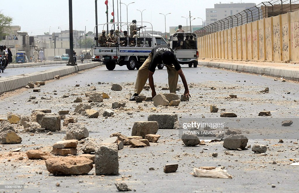 A Pakistani policeman removes stones and bricks on a street blocked by an angry mob during a protest against alleged target killings in Karachi on May 20, 2010. At least 17 people including two children have been killed in political clashes in Pakistan's financial capital Karachi in the past two days, a government official and police said. Police and paramilitary have been put on high alert and authorities closed all schools and colleges after the latest outbreak of politically related violence in Karachi, the biggest and richest city in Pakistan.