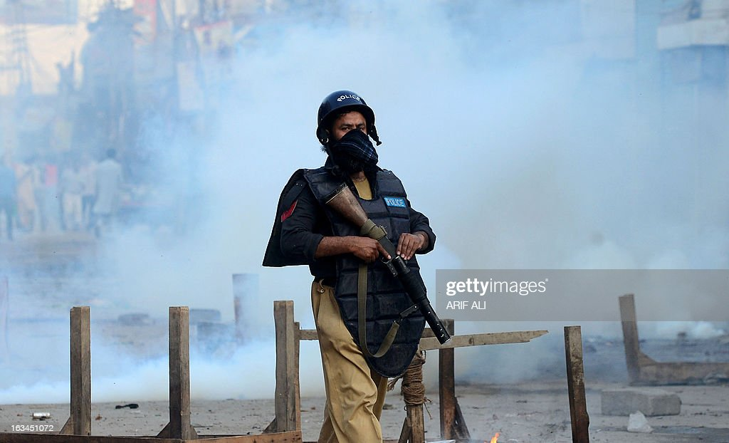 A Pakistani policeman returns after firing tear gas towards Christian demonstrators during a protest against the attack on the homes of members of the Christian community by Muslim demonstrators in Lahore on March 10, 2013. Christians demonstrated around Pakistan on March 10 to protest after a Muslim mob torched more than 100 Christian homes following allegations of blasphemy. More than 3,000 Muslims rampaged through Joseph Colony, a Christian area of the eastern city of Lahore, on March 9 after allegations that a Christian had made derogatory remarks about the Prophet Mohammed three days earlier.