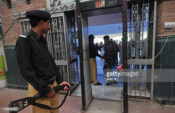 A Pakistani policeman searches a passenger at the Lahore railway station in Lahore on August 5 2013 A bomb exploded on a passenger train in central...