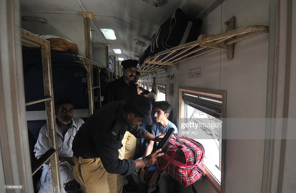 A Pakistani policeman searches a passenger's bag inside a train compartment in Lahore on August 5, 2013. A bomb exploded on a passenger train in central Pakistan on August 5, killing a toddler and wounding 13 others, officials said, in what the railways minister called 'an act of terrorism'. The device on the Shalimar Express from the eastern city of Lahore to Karachi went off as it passed through fields near the town of Toba Tek Singh in Punjab province.