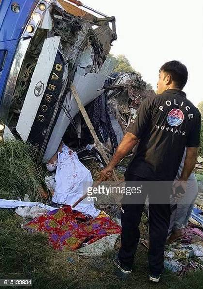 A Pakistani policeman stands at the scene of a fatal bus crash in Khanpur some 800 kilometres south of the capital Islamabad on October 17 2016 At...