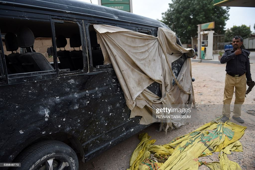 A Pakistani policeman stands beside a damaged vehicle in which a Chinese National was travelling, following a roadside bomb attack in Karachi on May 30, 2016. A Chinese worker and his Pakistani driver were wounded in the bomb attacked in Karachi on May 30, which has been claimed by ethnic nationalists opposed to plans for extensive Chinese investment, police said. / AFP / RIZWAN
