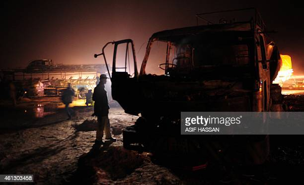 A Pakistani policeman stands beside wreckage of a burnt out oil taker and passenger bus following an accident along the Super Highway near Karachi...