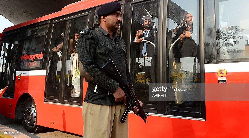 A Pakistani policeman stands guard as a brand-new Metrobus travels to the launch ceremony of the Metro Bus system in Lahore on February 10, 2013. Authorities in Pakistan on Sunday launched a 'Metro Bus' system in the second largest city, Lahore, the restive country's first major urban public transport scheme. AFP PHOTO/Arif ALI