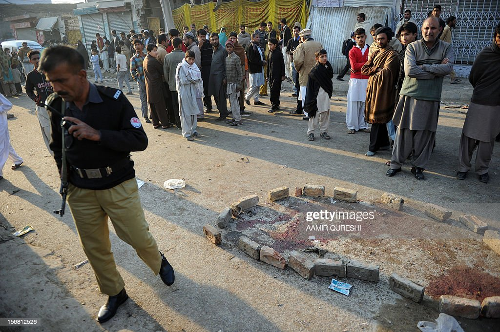 A Pakistani policeman stands guard at the site of an overnight suicide bomb attack on minority Shiite Muslims procession in Rawalpindi on November 22, 2012. A suicide bomber struck a night-time Shiite march in Pakistan, in the bloodiest attack of a day of violence that left at least 28 people dead as Islamic leaders gathered for a rare summit in Islamabad. Police in the garrison city of Rawalpindi near the capital said the attack on the procession of minority Shiite Muslims killed at least 16 people, after the suicide bomber blew himself up when he was stopped for a security check. AFP PHOTO/Aamir QURESHI