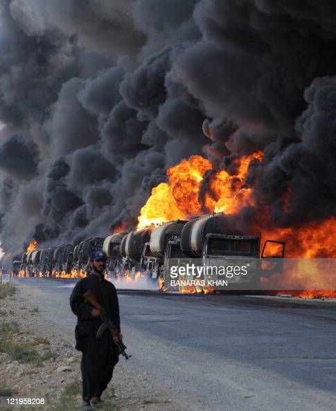 A Pakistani policeman stands guard beside burning NATO supply oil tankers following an attack by gunmen on the main highway at Kolpur village 25...