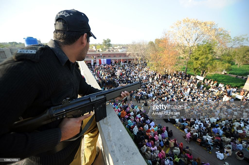 A Pakistani policeman stands guard during the funeral ceremony of slain Pakistani minister for minorities Shahbaz Bhatti in his native village...