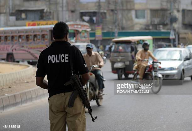 A Pakistani policeman stands guard following an attack on Muttahida Qaumi Movement opposition party legislator Rashid Godil in Karachi on August 18...
