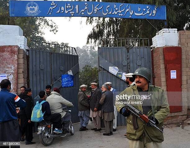 A Pakistani policeman stands guard outside a government school after schools in the city reopened following a Taliban attack in Peshawar on January...