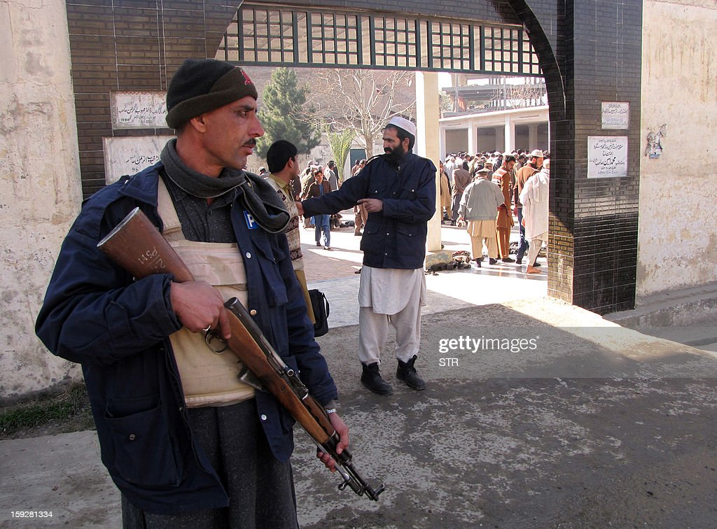 A Pakistani policeman stands guard outside a religious seminary after a day a bomb explosion in the outskirts of Mingora, the main town in the district, on January 11, 2013. An explosion at a religious gathering in Pakistan's northwestern Swat valley that killed 22 people and wounded more than 80 was caused by a bomb, officials said Friday.