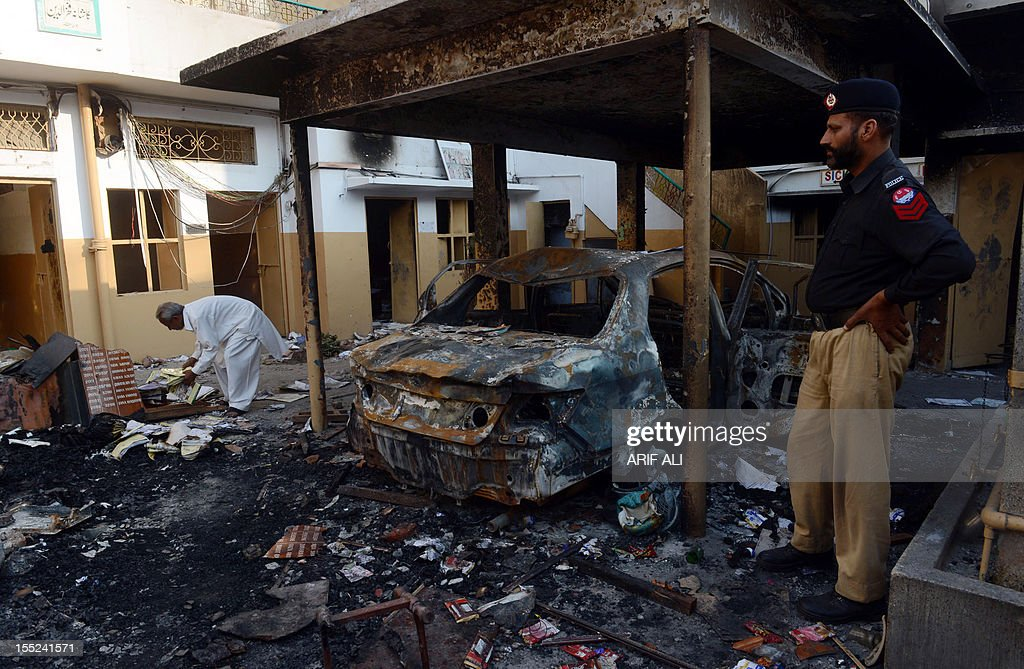 A Pakistani policeman stands next to wreckage of a burnt out a car at a school that was set fire by an angry mob, following a protest alleging the school gave a test that insulted the Prophet Mohammed, in Lahore on November 2, 2012. A Pakistani teacher at the centre of a blasphemy row was in hiding Friday as her school management denied all responsibility for the 'dirty act' and called for her to be punished. Arfa Iftikhar was forced into hiding after a furious mob stormed Farooqi Girls' High School in the eastern city of Lahore over a piece of homework she set that allegedly contained derogatory references to the Muslim prophet Mohammad.