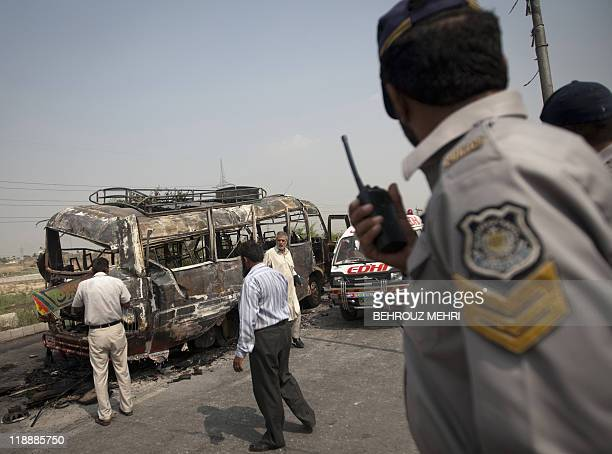 A Pakistani policeman talks on handheld radio near a burnt bus that was destroyed after the compressed natural gas cylinders powering it exploded...