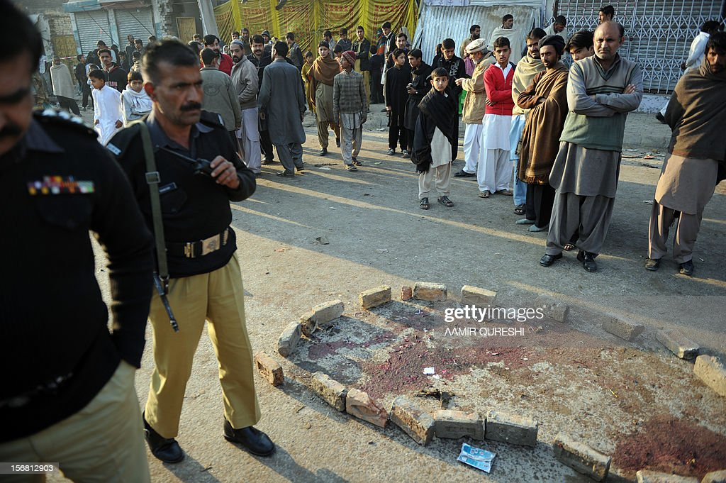Pakistani policemen and local residents gather at the site of an overnight suicide bomb attack on minority Shiite Muslims procession in Rawalpindi on November 22, 2012. A suicide bomber struck a night-time Shiite march in Pakistan, in the bloodiest attack of a day of violence that left at least 28 people dead as Islamic leaders gathered for a rare summit in Islamabad. Police in the garrison city of Rawalpindi near the capital said the attack on the procession of minority Shiite Muslims killed at least 16 people, after the suicide bomber blew himself up when he was stopped for a security check. AFP PHOTO/Aamir QURESHI