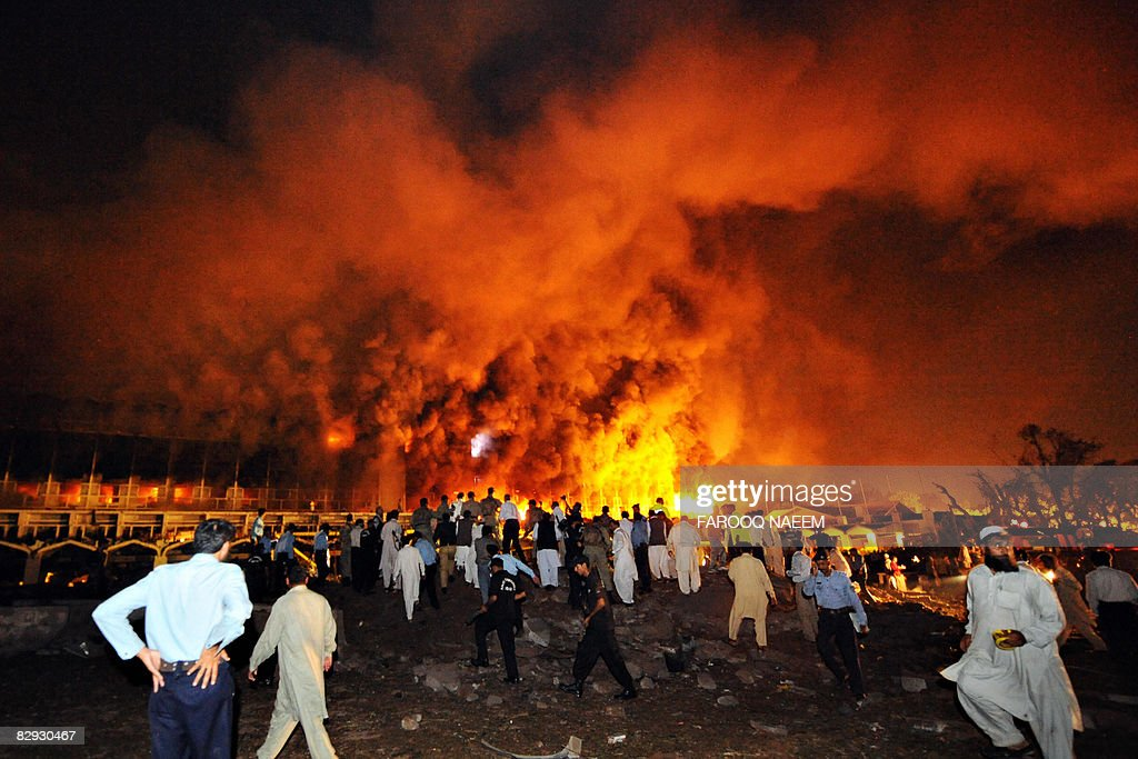 Pakistani policemen and onlookers gather as a cloud of smoke billows from the burning Marriott hotel following a powerful bomb blast in Islamabad on...