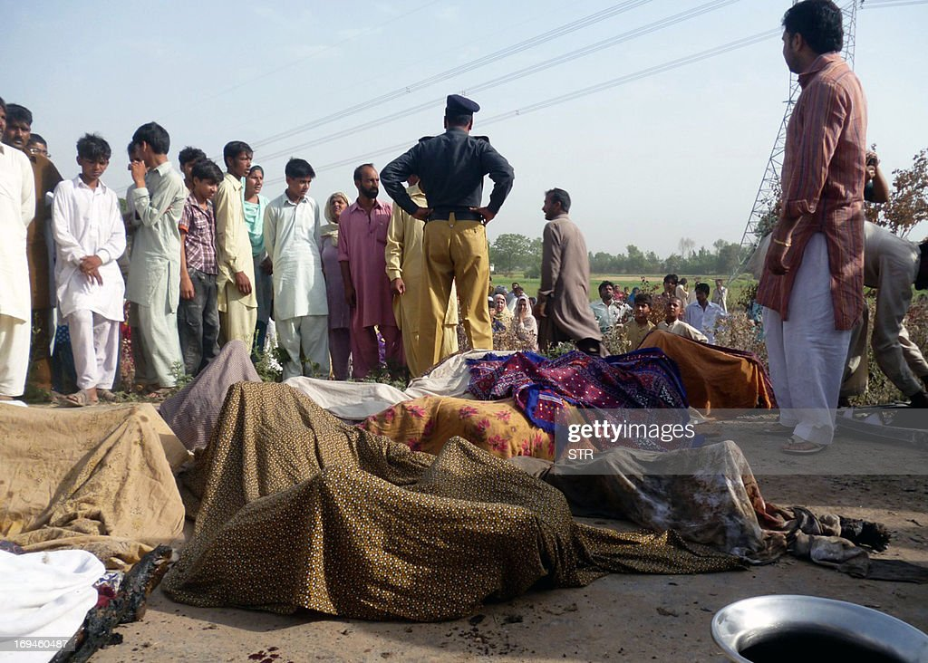 Pakistani policemen and villagers gather around the dead bodies of school children after the school van caught fire in Mangowal, some 185 kilometers from Islamabad on May 25, 2013. Sixteen children and a teacher were killed when their school van caught fire in central Pakistan on Saturday, police said.