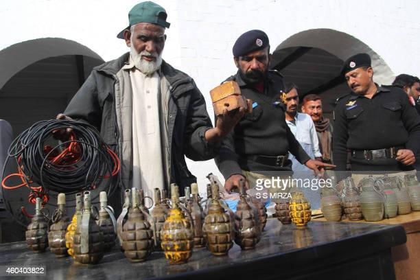 Pakistani policemen arrange weapons and explosives recovered from militants after a gun battle in the southern Muzaffargarh district some 350...