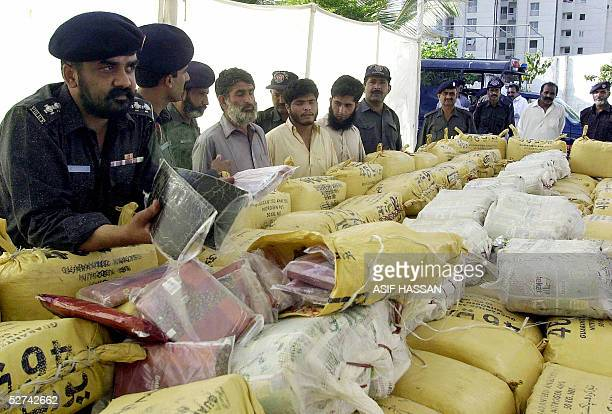 Pakistani policemen display the packets of hashish seized from an oil tanker and the three suspects who were arrested when the seizure was made in...