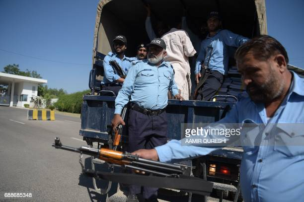 Pakistani policemen escort a truck carrying bundles of budget documents to the parliament where Pakistani Finance Minister Ishaq Dar presented the...