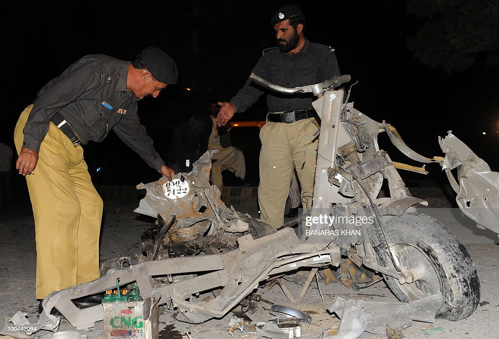 Pakistani policemen inspect a burnt motocycle on the bomb blast site in Quetta on May 24, 2010. Two people were killed and a dozen wounded, including several wedding party guests, when a bomb exploded in a rickshaw in Pakistan's southwestern Baluchistan province, police said. AFP PHOTO/Banaras KHAN