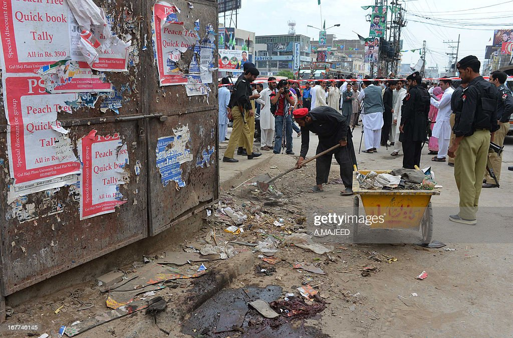 Pakistani policemen inspect the site of a bomb blast in Peshawar on April 29, 2013. A suicide bomber killed at least eight people and wounded 45 others when he rammed his motorcycle into a bus in Pakistan's northwestern city of Peshawar on Monday, police said.