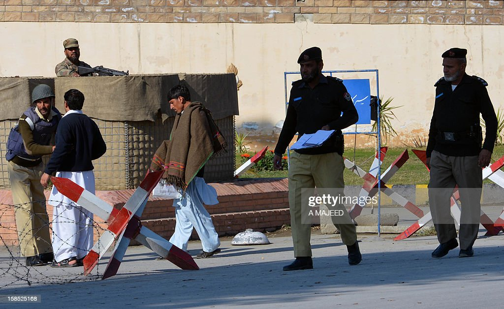 Pakistani policemen investigate a grenade attack site near the PAF Engineering Centre in Nowshera on December 18, 2012. According to security forces, unknown attackers riding on two motorbikes hurled two hand grenades near the PAF Engineering Centre that hurt ten people, including five security men and five civilians.