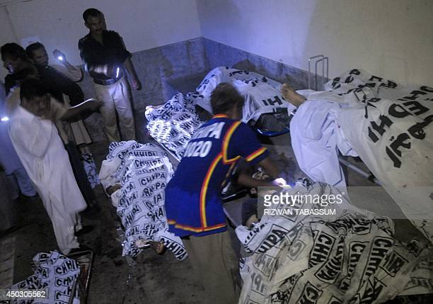Pakistani policemen look at the bodies of security personnel at a hospital following a militants attack on Karachi airport terminal in Karachi on...