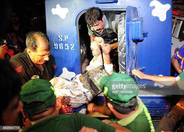 Pakistani policemen move an injured colleague outside Karachi airport terminal after the militants' assault in Karachi late on June 8 2014 Heavily...