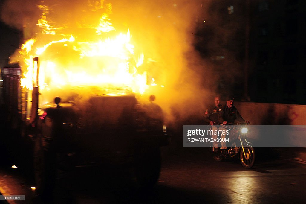 Pakistani policemen patrol on a motorbike past a burning truck torched by an angry mob following sectarian killing in Karachi on November 6, 2012. Gunmen shot dead three Shiite Muslims and wounded two others on Tuesday in a fresh sectarian attack in Pakistan's troubled southwestern province of Baluchistan, police said.