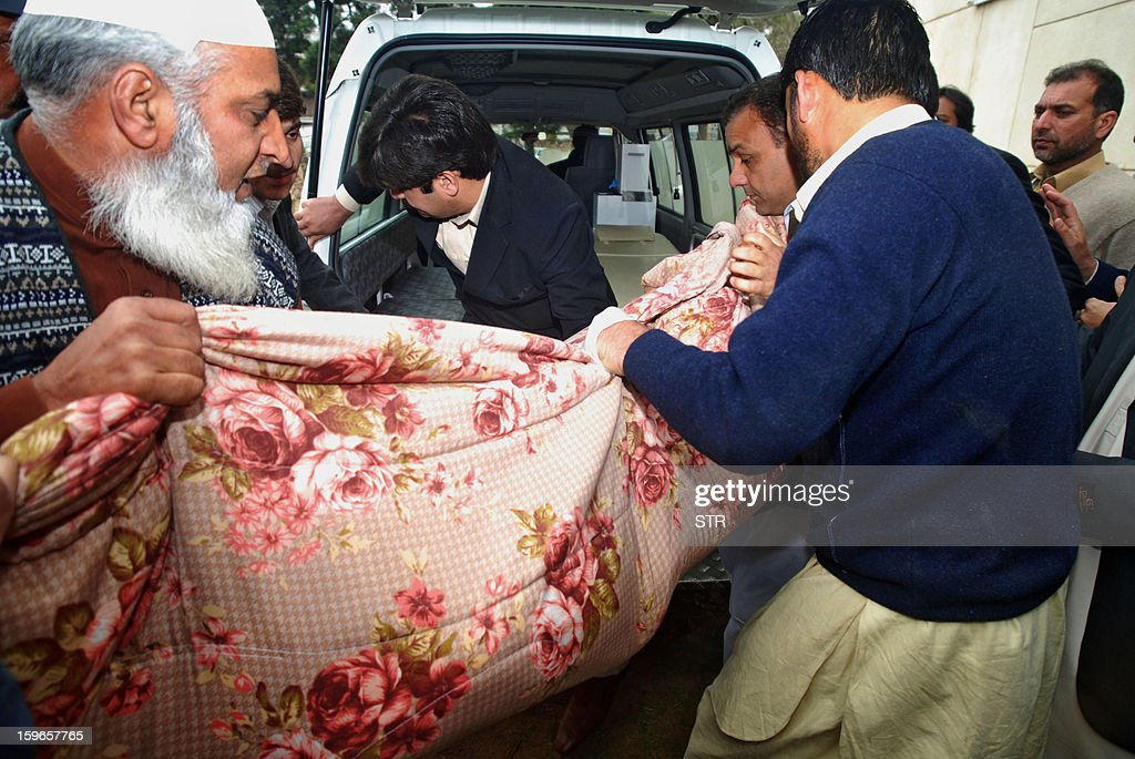 Pakistani policemen shift the dead body of Kamran Faisal, who was investigating a corruption scandal involving Prime Minister Raja Pervez Ashraf and was found dead in the government hostel in Islamabad on January 18, 2013. A case officer investigating a corruption scandal involving Prime Minister Raja Pervez Ashraf was found dead on Friday in Islamabad, officials said.