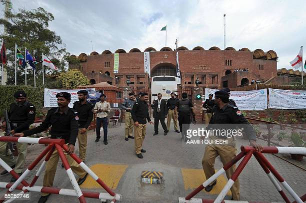 Pakistani policemen stand guard as a bus carrying security personnel enters The Gaddafi Stadium after masked gunmen attacked the Sri Lankan team in...