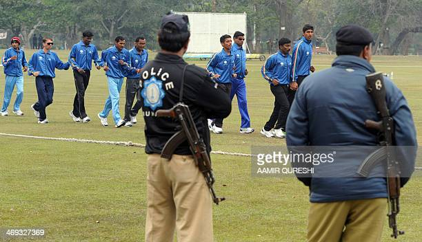 Pakistani policemen stand guard as Indian blind cricketers warm up at the BagheJinnah cricket ground in Lahore on February 14 2014 Indian blind...