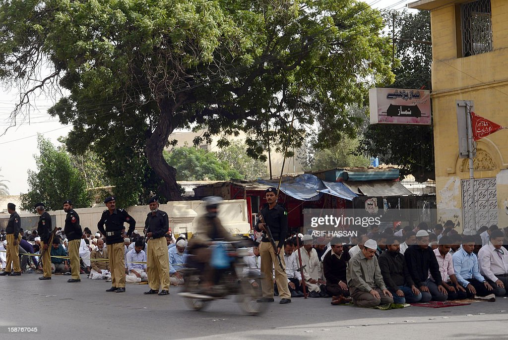 Pakistani policemen stand guard as Muslims offer Friday prayers at the roadside in Karachi on December 28, 2012. Pakistan shut down mobile and wireless phone services on December 28 in the commercial capital Karachi and beefed up security to prevent possible terror attacks, officials said. AFP PHOTO/Asif HASSAN