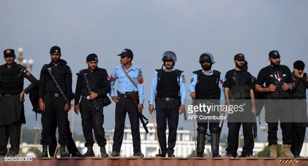 Pakistani policemen stand guard atop a container blocking a street leading to the Presidential palace during a protest rally by tribesmen in...