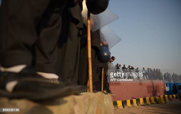 Pakistani policemen stand guard atop containers blocking a street leading to the Presidential palace during a protest rally by tribesmen in Islamabad...